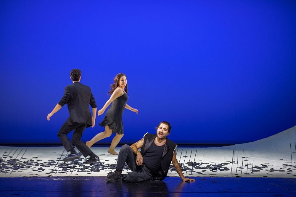 Szene aus dem Theaterstück, blauer Hintergrund, ein Mann sitzt und singt, eine Frau und ein Mann laufen lachend hinter einander her, die ganze Szene spielt auf einem überdimensionalen Notenblatt in schwarz-weiß, alle Akteure sind schwarz gekleidet