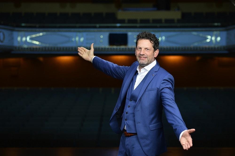 Intendant Aron Stiehl steht im Theater und breitet die Arme aus um die Zuschauer willkommen zu heißen, er lächelt und trägt einen blauen Anzug und ein weißes Hemd