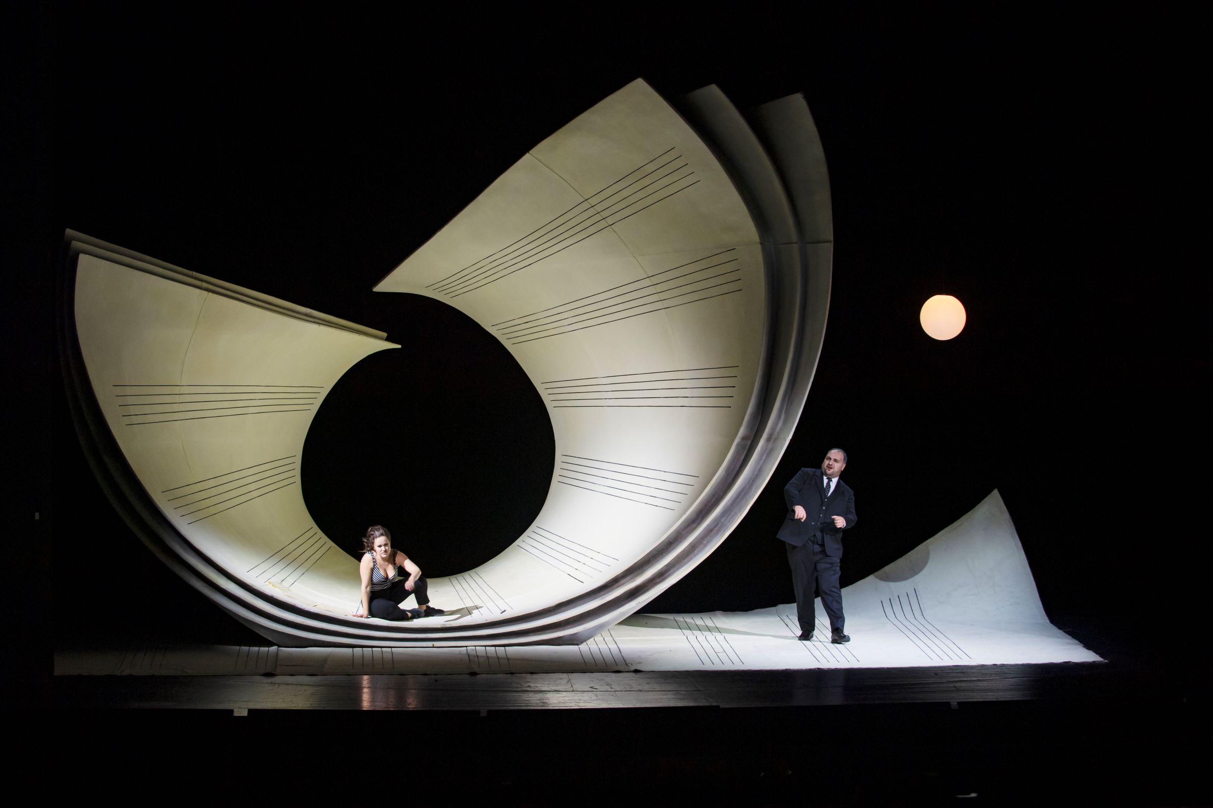 Szene aus il barbiere di siviglia, eine Frau sitzt in einem überdimensionalen, zusammengerollten Notenblatt, daneben steht ein Mann und singt, beide sind schwarz gekleidet