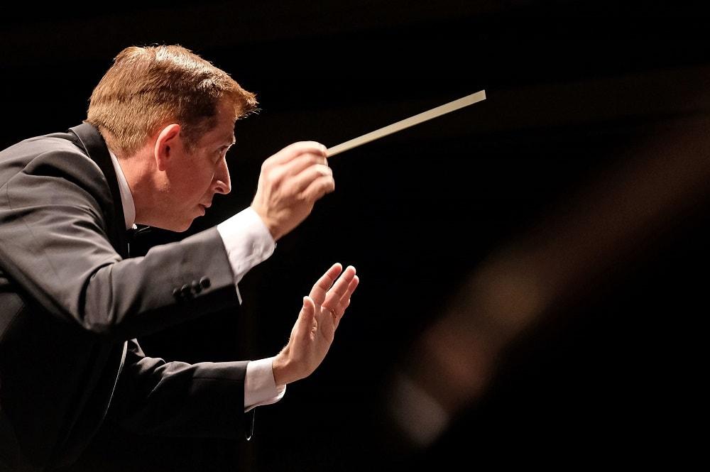 neuer Chefdirigent des Stadttheater Klagenfurt, Nicholas Milton mit Taktstock in der Hand und die Hand erhoben, er blickt auf sein Orchester und ist sehr konzentriert