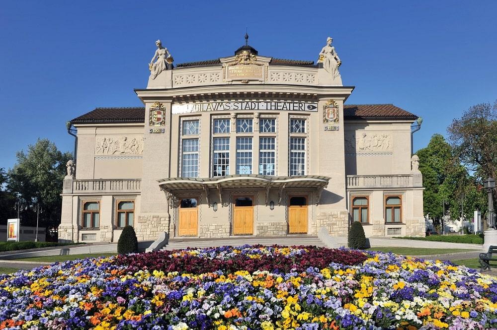 das Stadttheater Klagenfurt an einem schönen Sommertag, Front des Stadttheaters, Frauenstatuen links und recht am Dach, Blumenrendeau im Vordergrund mit vielen bunten Blumen, strahlend blauer Himmel