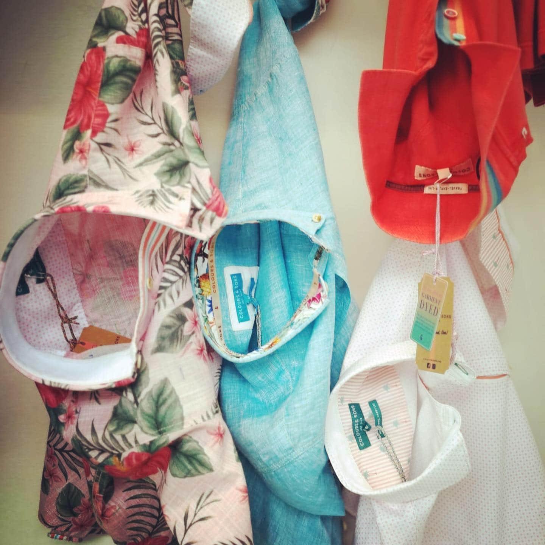 Leinenhemden in verschiedenen Farben wie hellblau, weiß, orange sowie weiß mit grünen Blättern und rotem Hibiskusprint