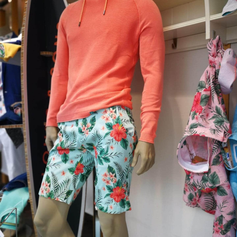 Sommeroutfit für Herren mit Bermudashort in türkis mit Blättern und Blumenprint in grün und orange, dazu ein oranger, dünner Kapuzensweater