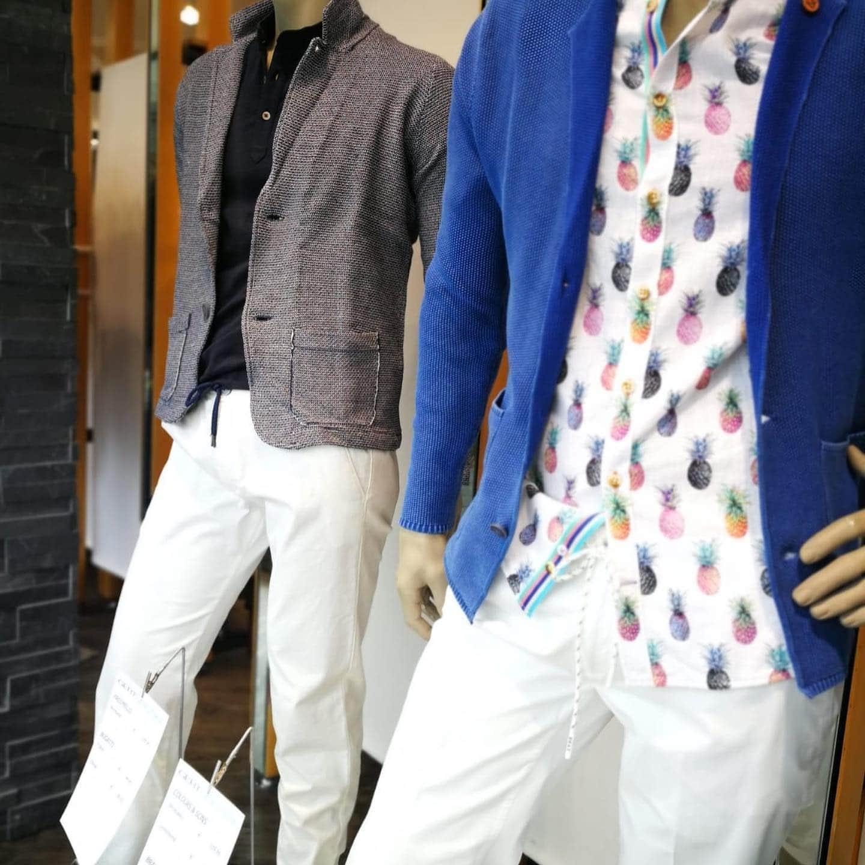 zwei Herrenoutfits auf Schaufensterpuppen, beide tragen weiße Leinenhosen, dazu einmal ein weißes Hemd mit bunten Ananas, dazu eine blitzblaue Strickjacke, das andere Modell zeigt ein schwarzes Poloshirt mit grauem, grob gewebtem Sweatblazer