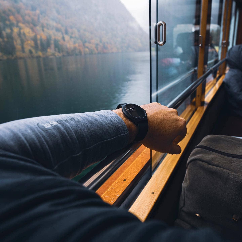 Ein Männerarm mit Anicon Armbanduhr lehnt an einem offenen Zugfenster, dahinter ein See