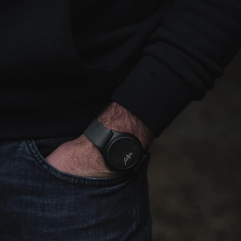 in eine Hosentasche eingesteckte Männerhand mit schwarzer Anicon Armbanduhr
