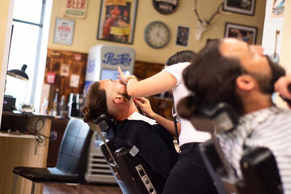 2 Männer sitzend auf einem Friseurstuhl nach hinten gelehnt, beiden wird der Bart geschnitten