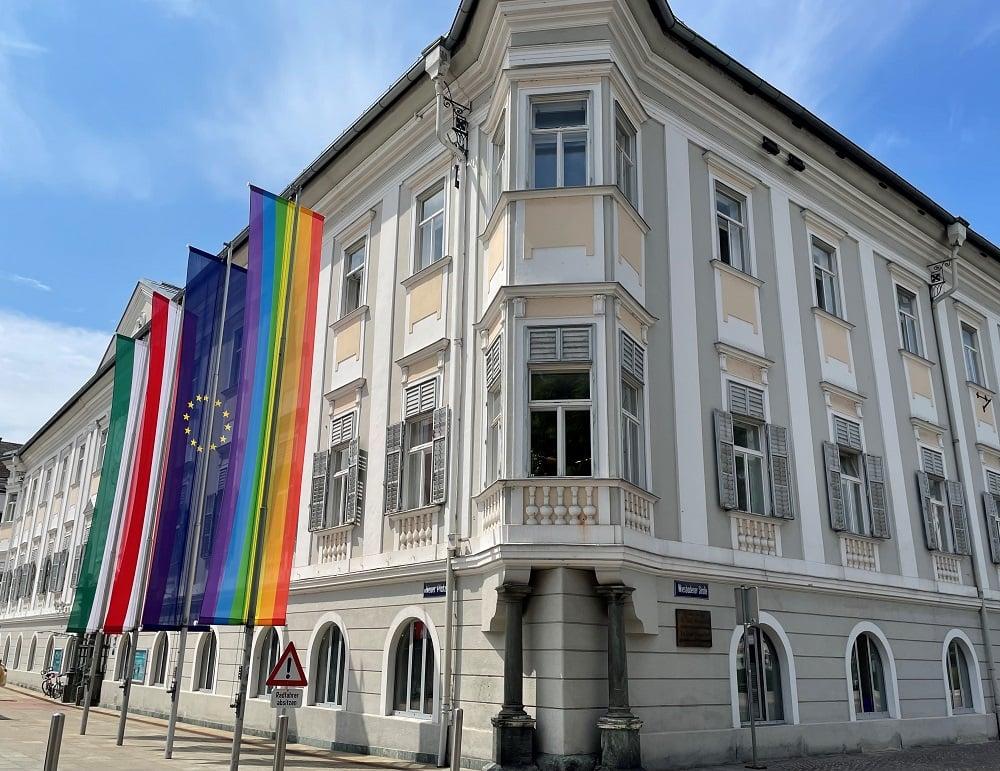 Fasade des Rathauses in Klagenfurt mit gehissten Flaggen von Italien, Österreich, Europa und der Regenbogenflagge