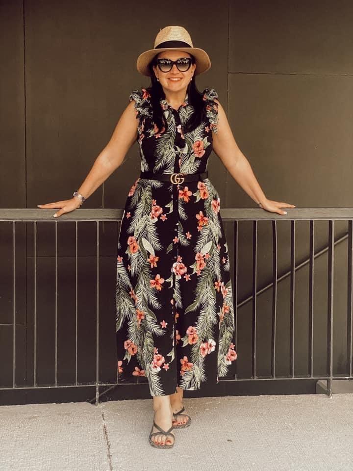 schwarzhaarige Frau mit einem Strohhut und einer schwarzen Sonnenbrille. Sie trägt ein knöchellanges Sommerkleid in schwarz mit Blättern und Blumenprint, das vorne mit einer Knopfleiste geschlossen ist, dazu Flip Flips