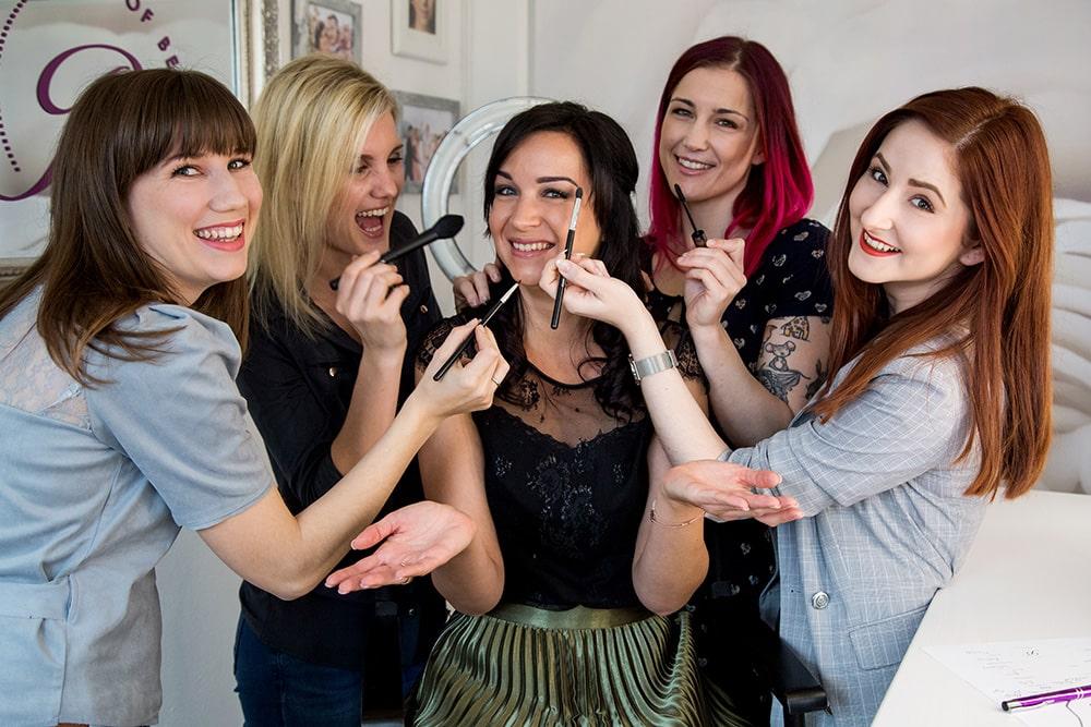 Beautyworkshop Schlussfoto, Belinda Wrann sitzt auf einem Hocker, um sie herum vier Teilnehmerinnen, die so tun als würden sie sie jetzt schminken