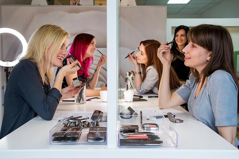 Beauty Workshop bei Belinda Wrann, vier Damen sitzen vor einem Spiel und schminken sich unter der Anleitung von Belinda