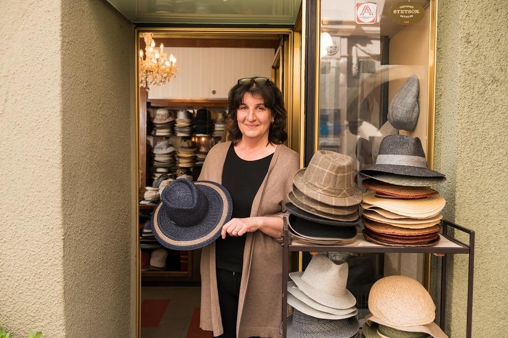die Inhaberin des Geschäftes Modellhüte Luise lehnt am Türranhmen ihres Geschäfts in der Hand einen schwarzen Strohhut mit breiter Krempe und einem beigen Streifen, neben ihr ein Regal mit vier Stapeln mit Hüten aus unterschiedlichem Material