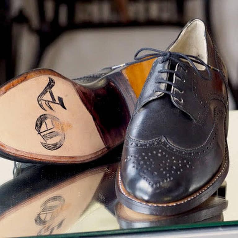schwarzer Lederschuh in Nahaufnahme und zweiter Schuh mit Initialien auf der Ledersohle