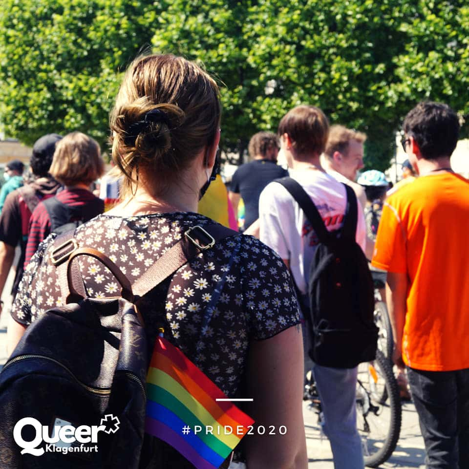 Rückansicht einer Frau mit Rucksack in dem eine Regenbogenfahne steckt, davor einige andre Menschen