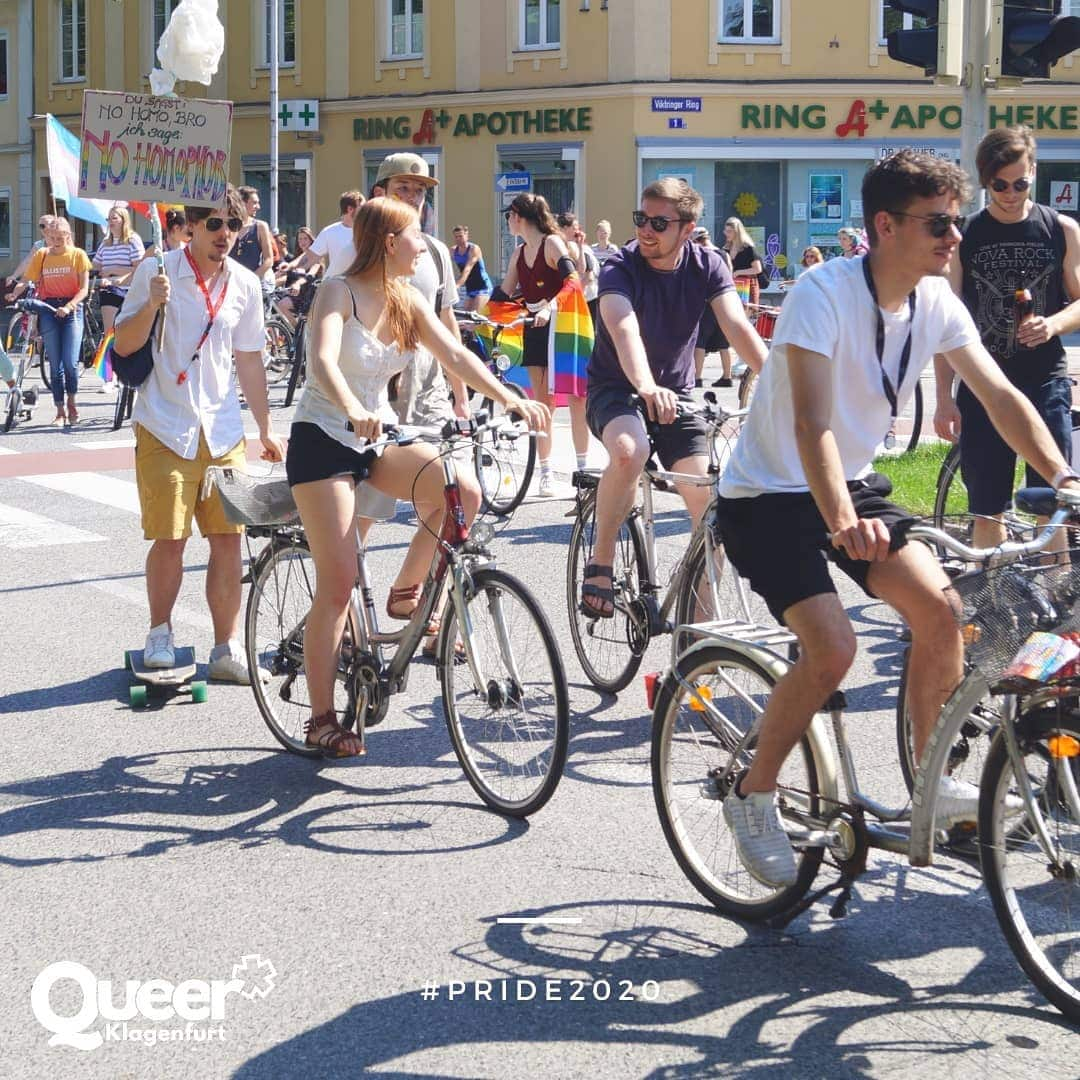 Schnappschuss der Fahrrade Regenbogenparade mit Frauen und Männern auf Fahrrädern, einige halten Regenbogenfahnen und Spruchtafeln in de Hand
