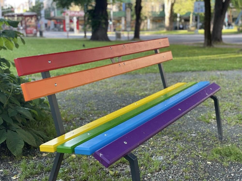 Parkbank in Regenbogenfarben vor der Kelag Klagenfurt, im Hintergrund Bäume und Sträucher