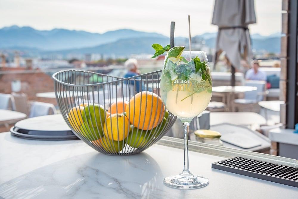 Obstschale und ein gekühlter Drink auf einer Bar, im Hintergrund die Stadt Klagenfurt