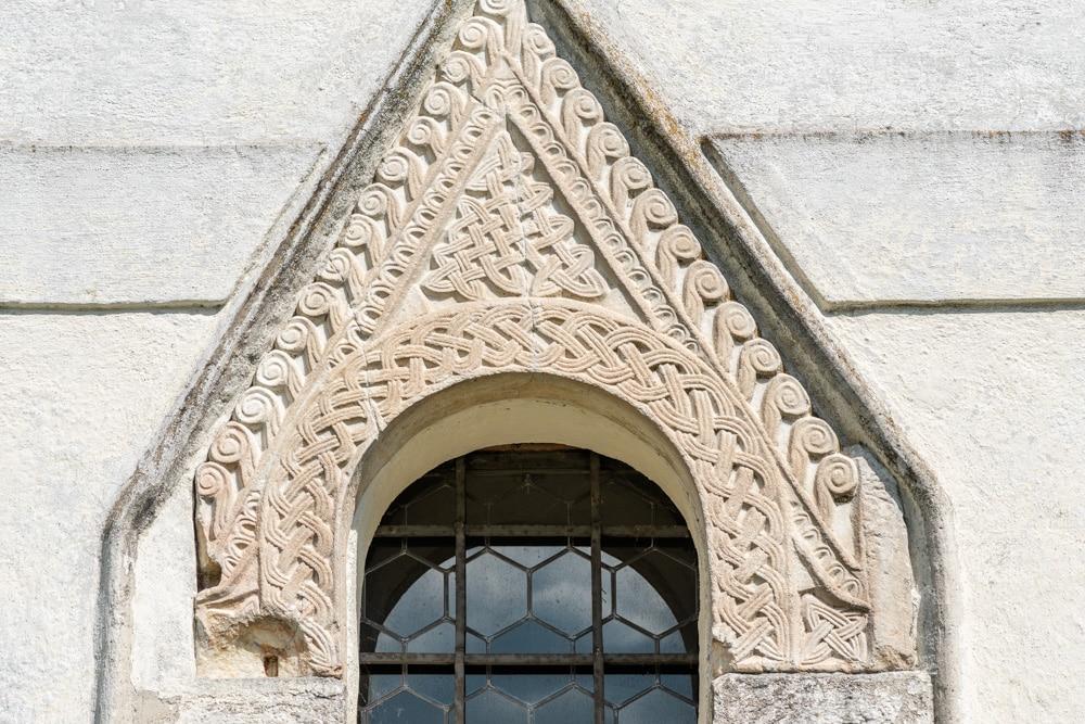 Auf der West-Fassade der Kirche sind über dem Kirchenportal zwei großartige karolingische Flechtwerksteine eingemauert