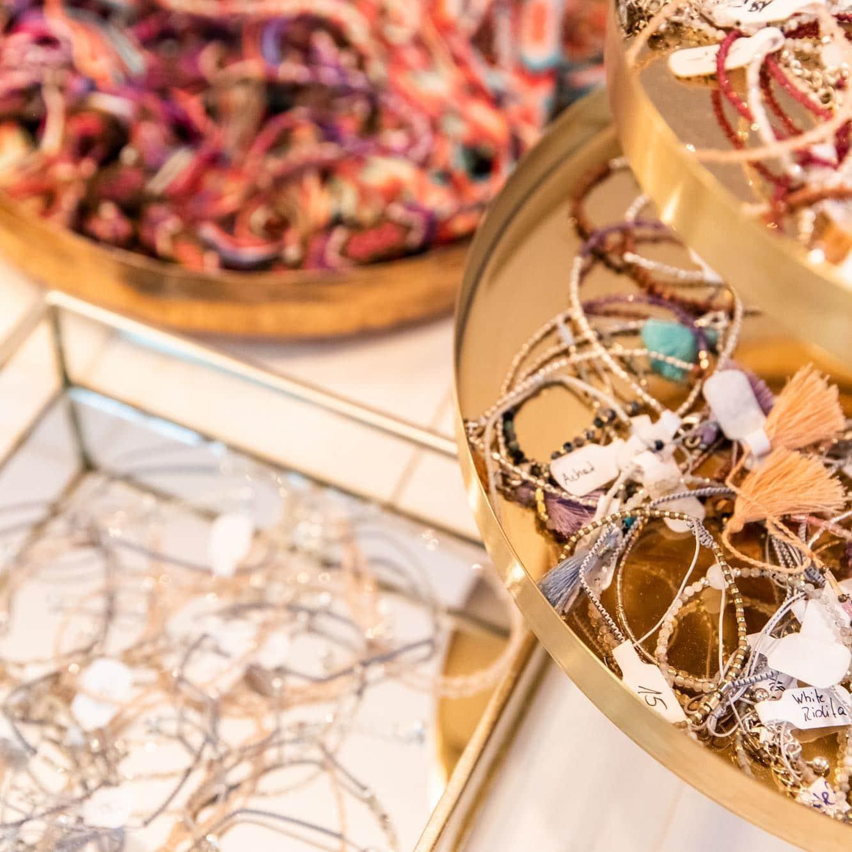 goldene Schüsseln gefüllt mir Armbändern und Ketten in verschiedenen Farben, mit Glasperlen und Quasten
