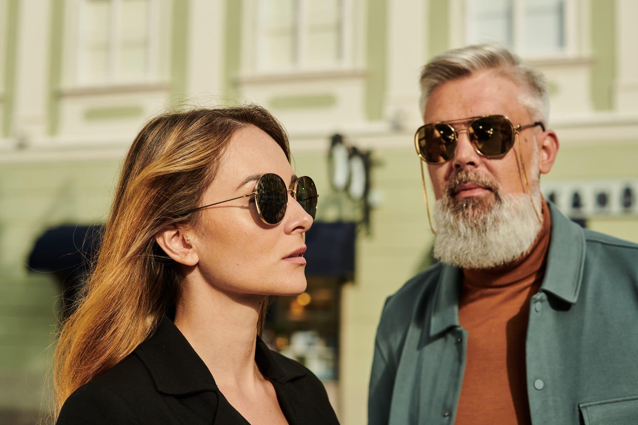zwei Personen, eine Dame und ein Herr mit großen, runden Sonnenbrillen mit goldenen Rahmen und schwarzen, verspiegelten Gläsern
