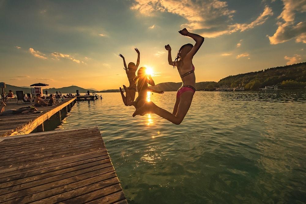 Abendstimmung im Strandbad Klagenfurt, die Sonne steht tief, man sieht einen Abschnitt der Brücke, auf dem Menschen liegen, im Vordergrund springen drei Mädchen mit erhobenen Händen ins Wasser