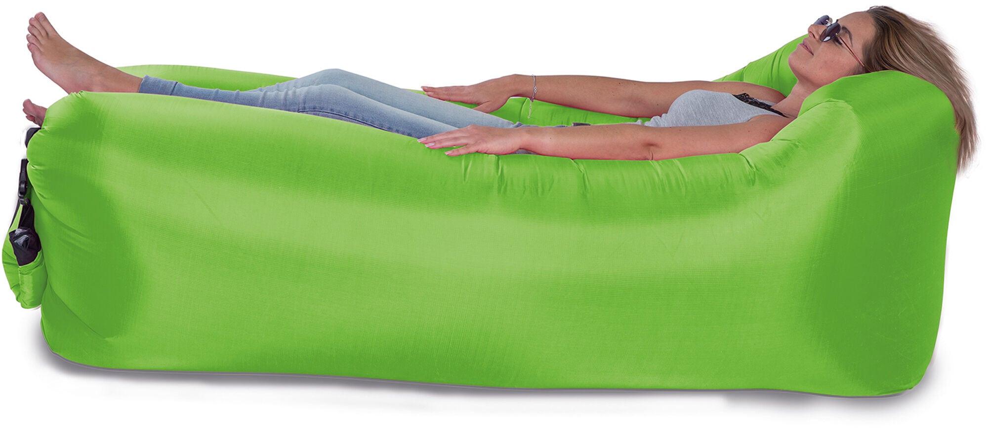 aufblasbarer Liegestuhl in grün auf dem eine Frau mit Sonnenbrille liegt, sie trägt Jeans und ein Shirt