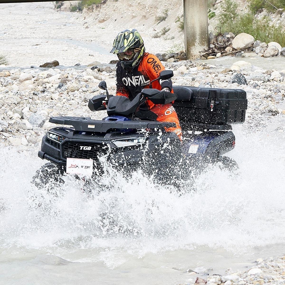ein Mann fährt mit einem Quad und Schutzkleidung durch einen Bach