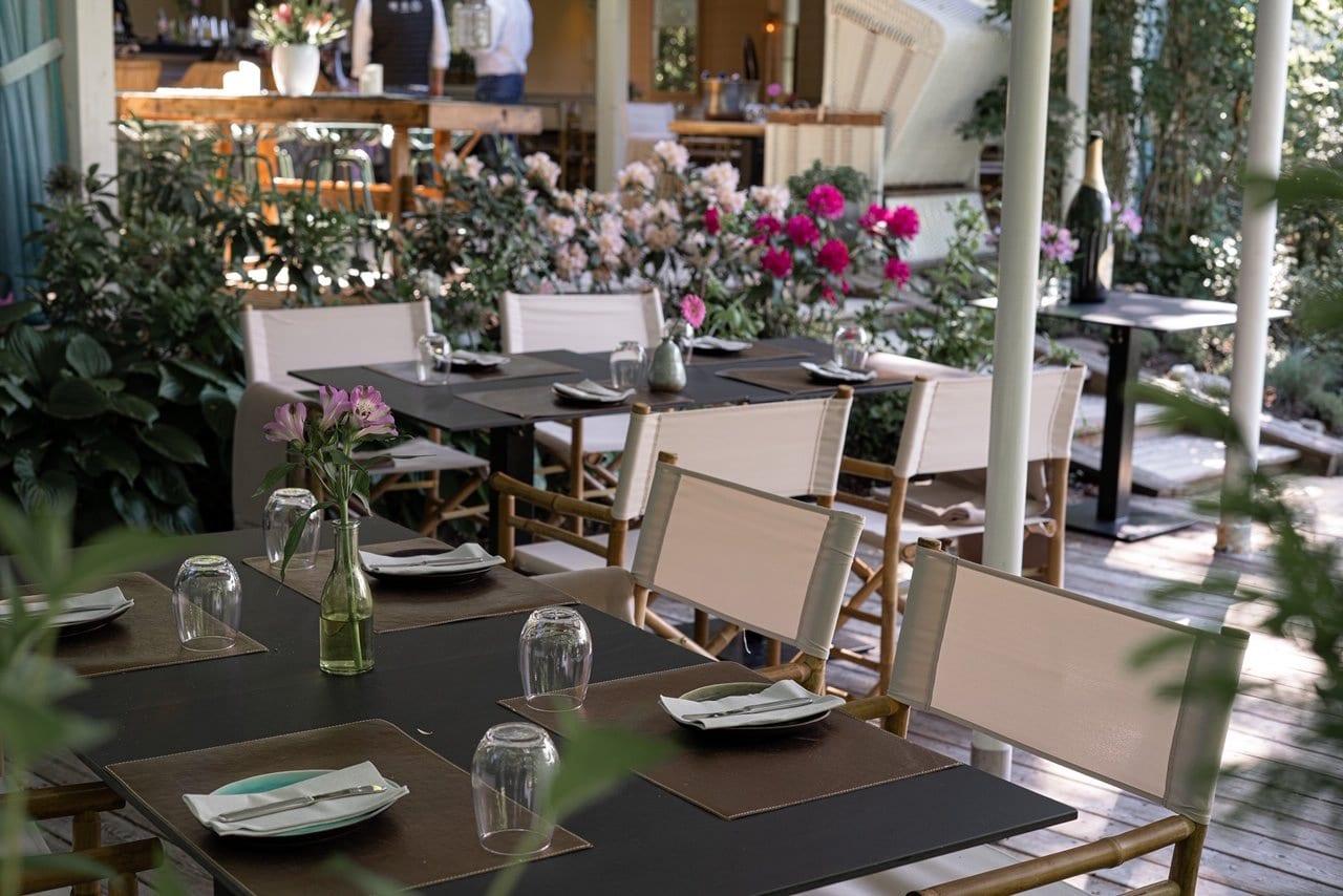 Blick auf die Terrasse im Restaurant 151er, auf den gedeckten Tischen stehen Blumenvasen, es gibt Mittagessen und Abendessen