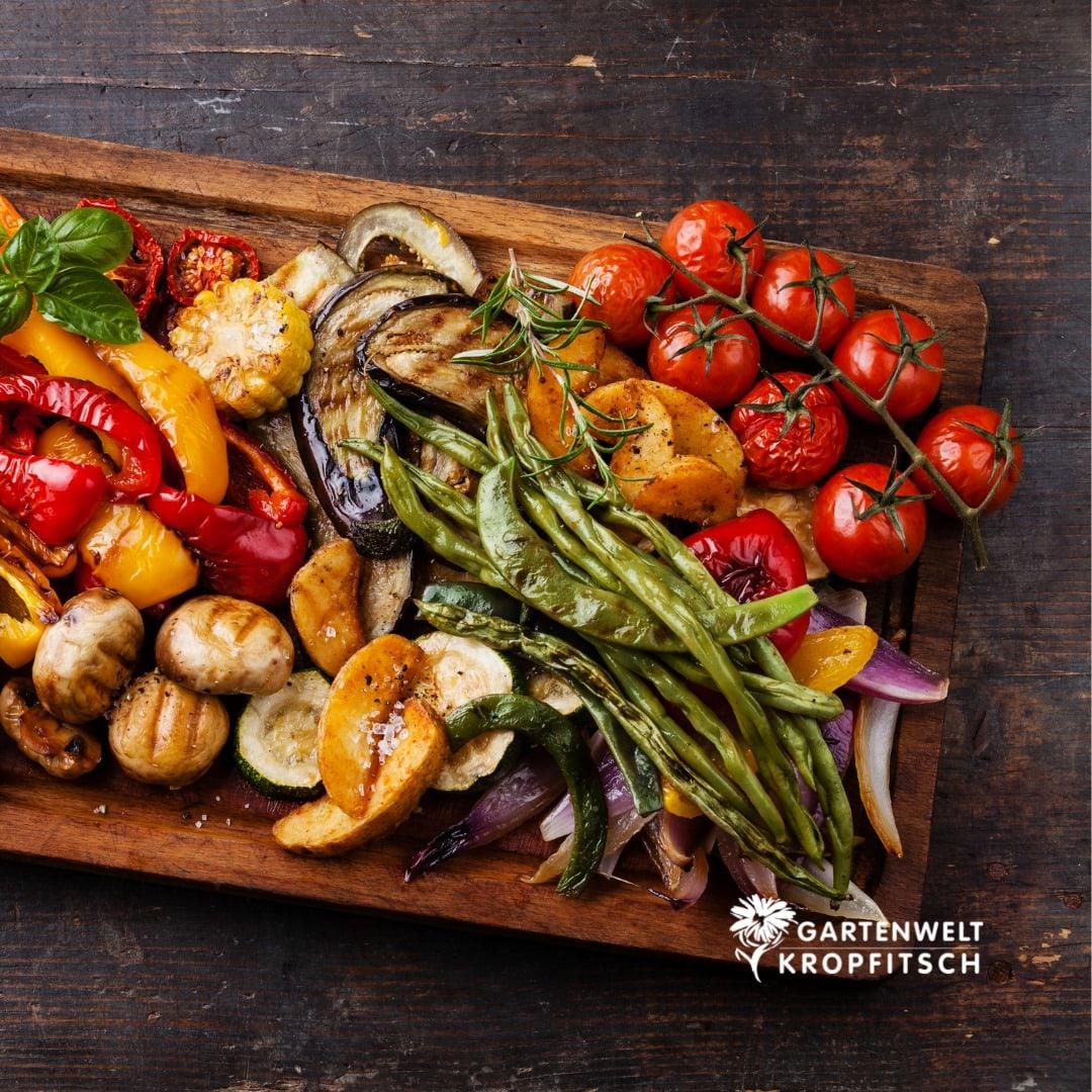 perfekt gegrilltes Gemüse mit einem Grill der Gartenwelt Kropfitsch auf einem Holzbrett angerichtet, Tomaten, Mais, Champignons, Kartoffel, Bohnen