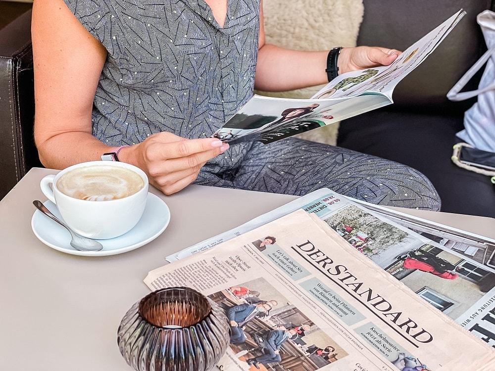 Frauenhände halten ein Magazin, auf dem Tisch liegen Tageszeitungen, daneben steht eine große Schale mit Kaffee und Milchschaum