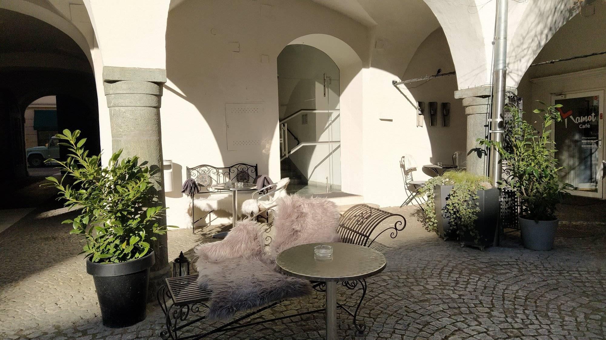 der Gastgarten des Kamot Cafés mit Eisensitzmöbeln und Grünpflanzen