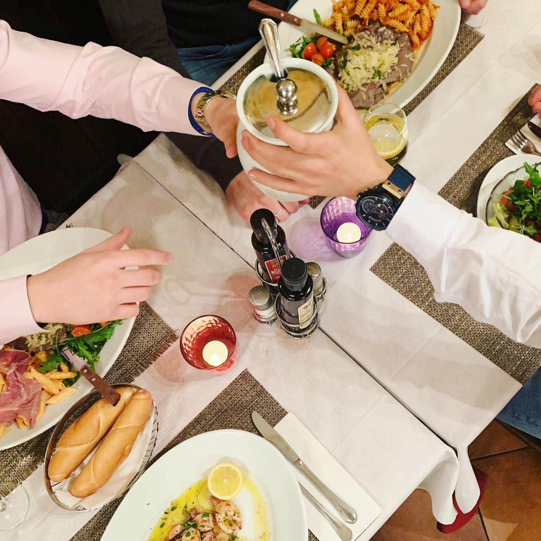 ein Blick auf den klassisch, italienisch gedecktenTisch in der Osteria dal Conte mit Pasta, Essig, Öl und einer Schüssel Parmesan die von einer Hand in eine andere gereicht wird, hier kann man mittags und abends gut essen
