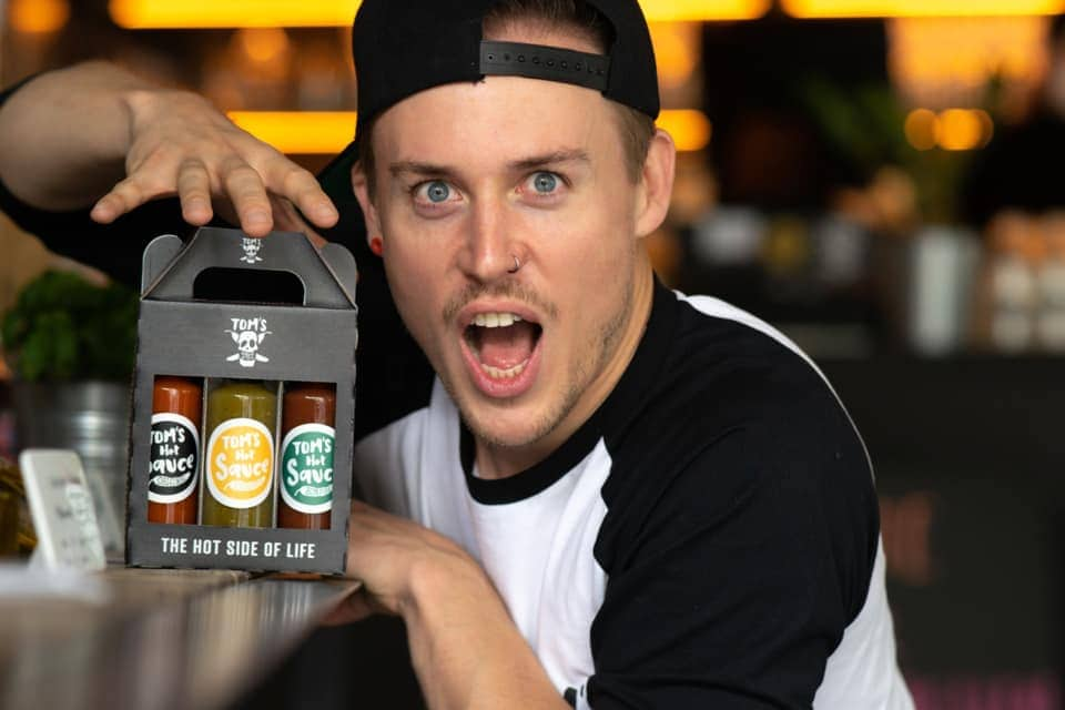 Tomas Hlatky, Inhaber von Toms Hot Stuff, handgemachten, veganen, nachhaltig produzierten Chillisaucen hält eine Schachtel mit drei verschiedenen Chillisaucen in die Kamera, sein Gesichtsausdruck zeigt, dass die Saucen scharf sind