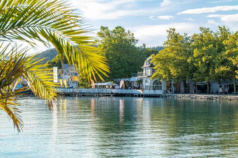 Blick auf die Villa Lido, im Vordergrund eine Palme und er blaue Wörthersee, ein Schiff legt an