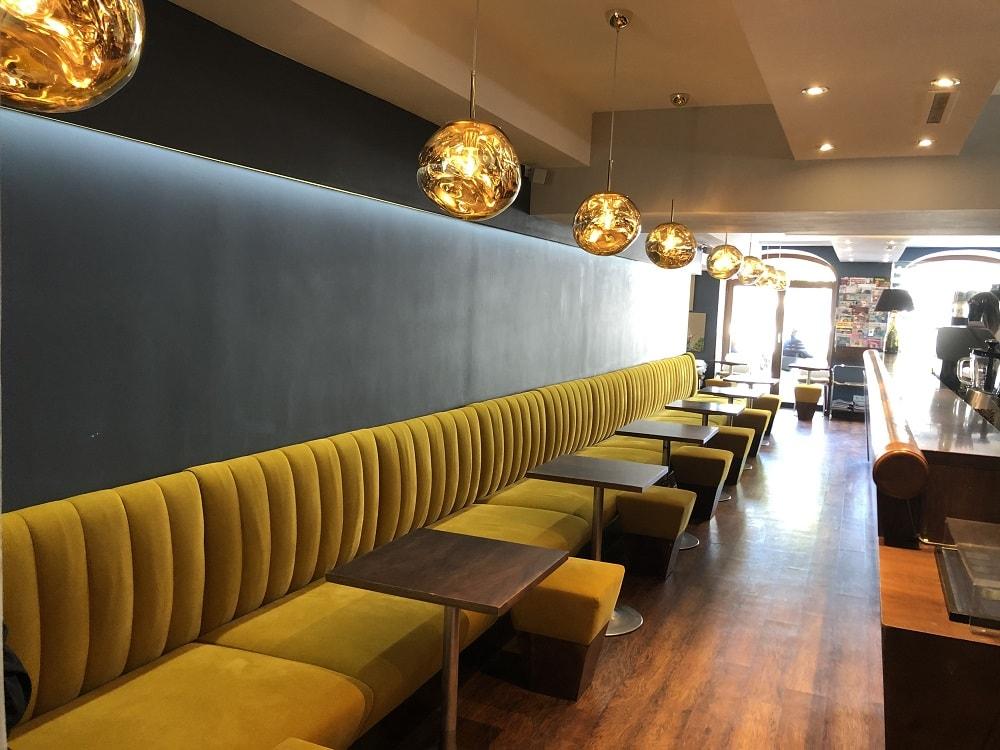 Blick ins Café am Platz mit einer durchgehenden, an der Wand verbauten Couch aus gelbem Samt, dazu kleine, eckige Bistrotische und goldene, kugelförmige Lampen, am rechten Bildrand ist die Theke zu sehen