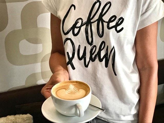 der Bildausschnitt zeigt die Arme und das T-Shirt einer Frau, die einen Cappuccino mit Milchschaum in der Hand hält, auf den ein Blatt gezeichnet ist, auf ihrem T-Shirt steht coffee queen