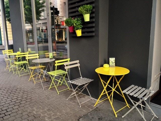 der Como Gastgarten mit Bistrotischen und Stühlen in grau und gelb, darüber hängen Grünpflanzen