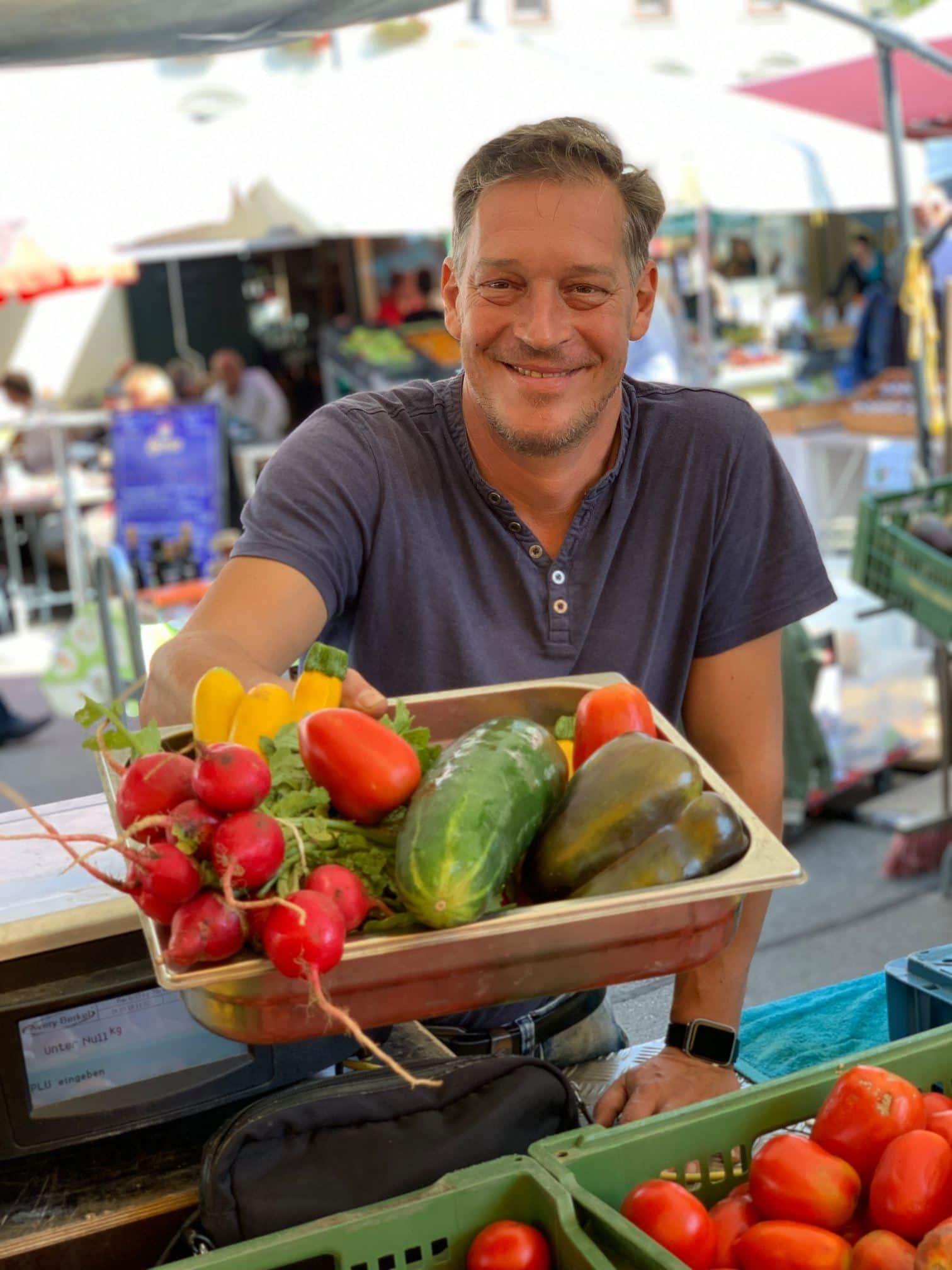 Nikolaus Toschkov von der Gärtnerei reicht dem Betrachter mit einem Lächeln einen Gemüsekorb, darin befinden sich Radischen, Zucchini, Paprika und Gurken