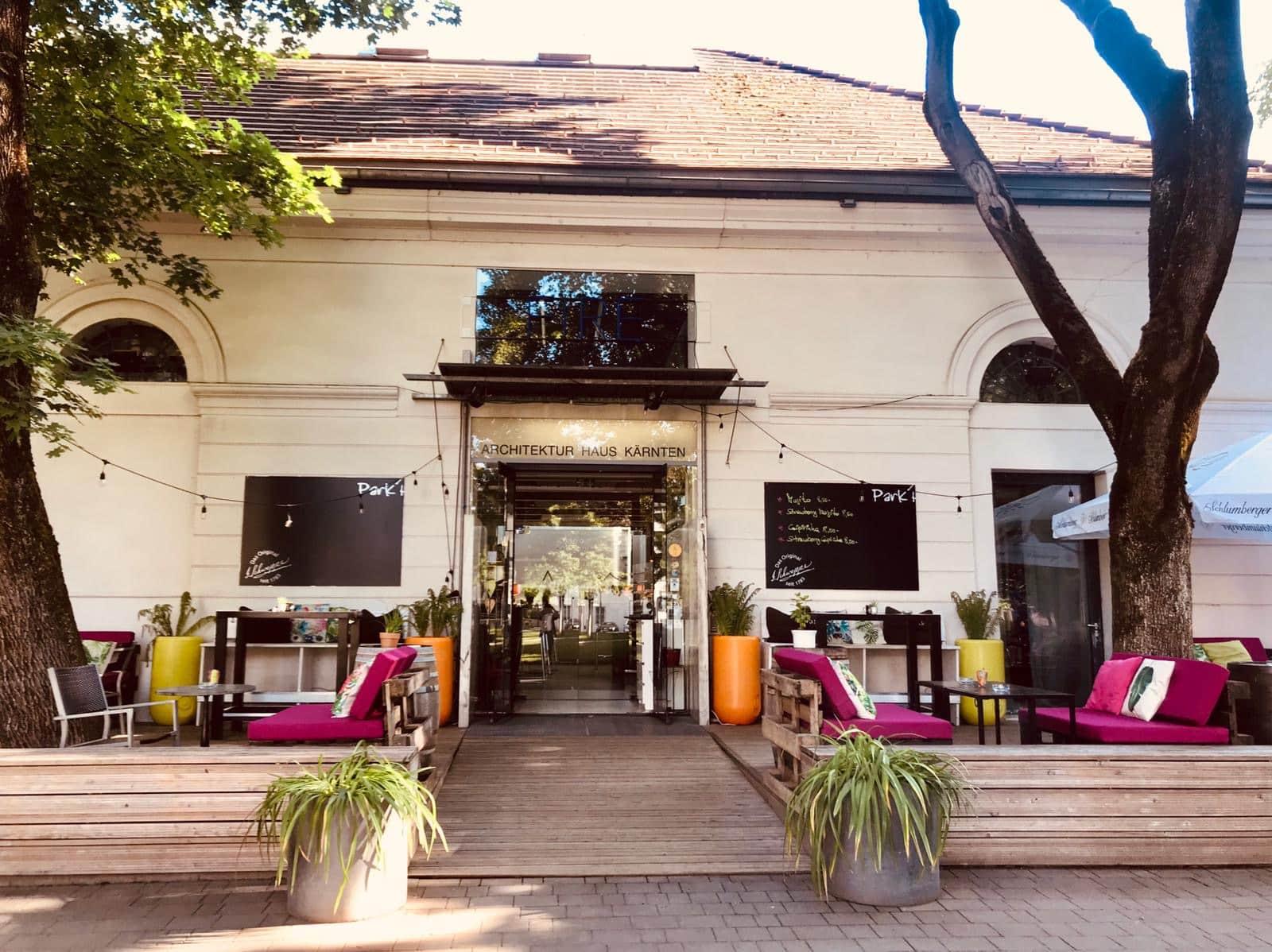 Außenansicht vom Parkhaus mit Schriftzug Architektur Haus Kärnten, im Vordergrund zwei Grünfplanzen, die die Rampe zum Eingang zieren, die Sitzmöbel sind mit pinken und grünen Sitzpölstern bedeckt.