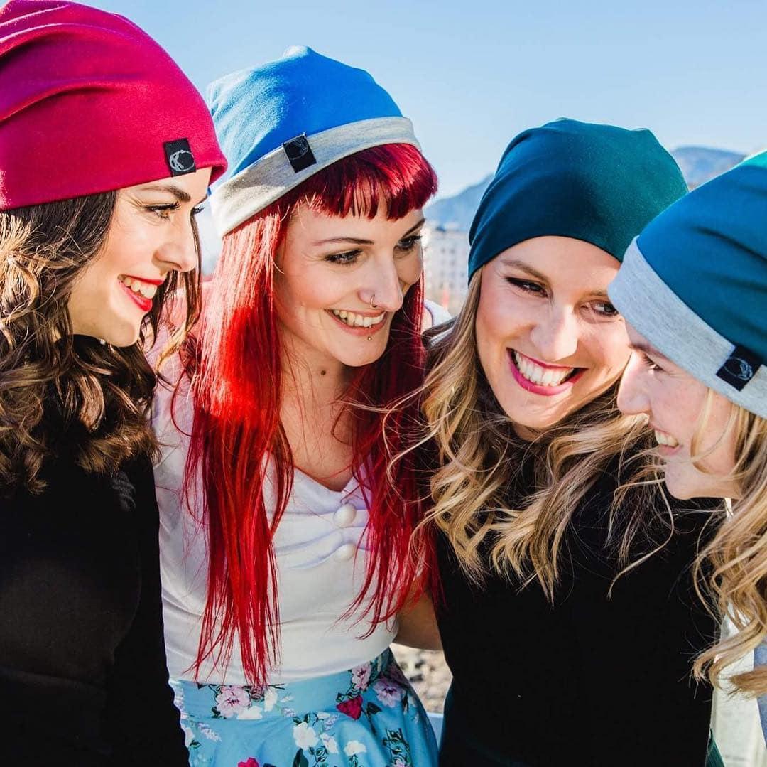 handemachte Wendemützen, Beanies aus Jersey der Firma die Fashionista aus Klagenfurt, vier Freundinnen stehen im Kreis und lachen sich gegenseitig zu, sie tragen Beanies in verschiedenen Farben wie rot, blau, grau und grün