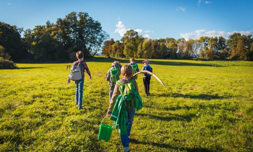 Freiluft Workshop bei Erlebensraum Natur, die Teilnehmer gehen mit Rucksack über eine Wiese