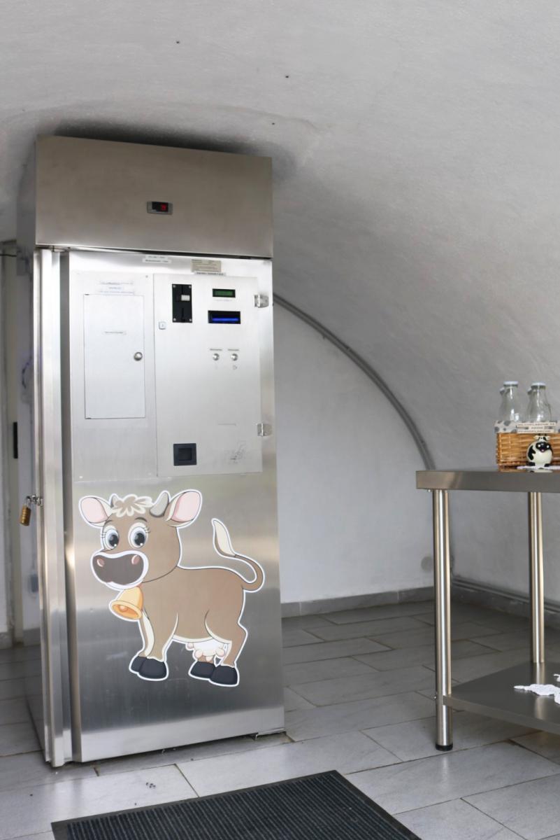 der 24 Stunden Frischmilchautomat am Hoislhof aus Edelstahl, daneben stehen Milchflaschen aus Glas, am Automaten klebt ein Aufkleber einer Comic-Kuhl mit goldener Glocke