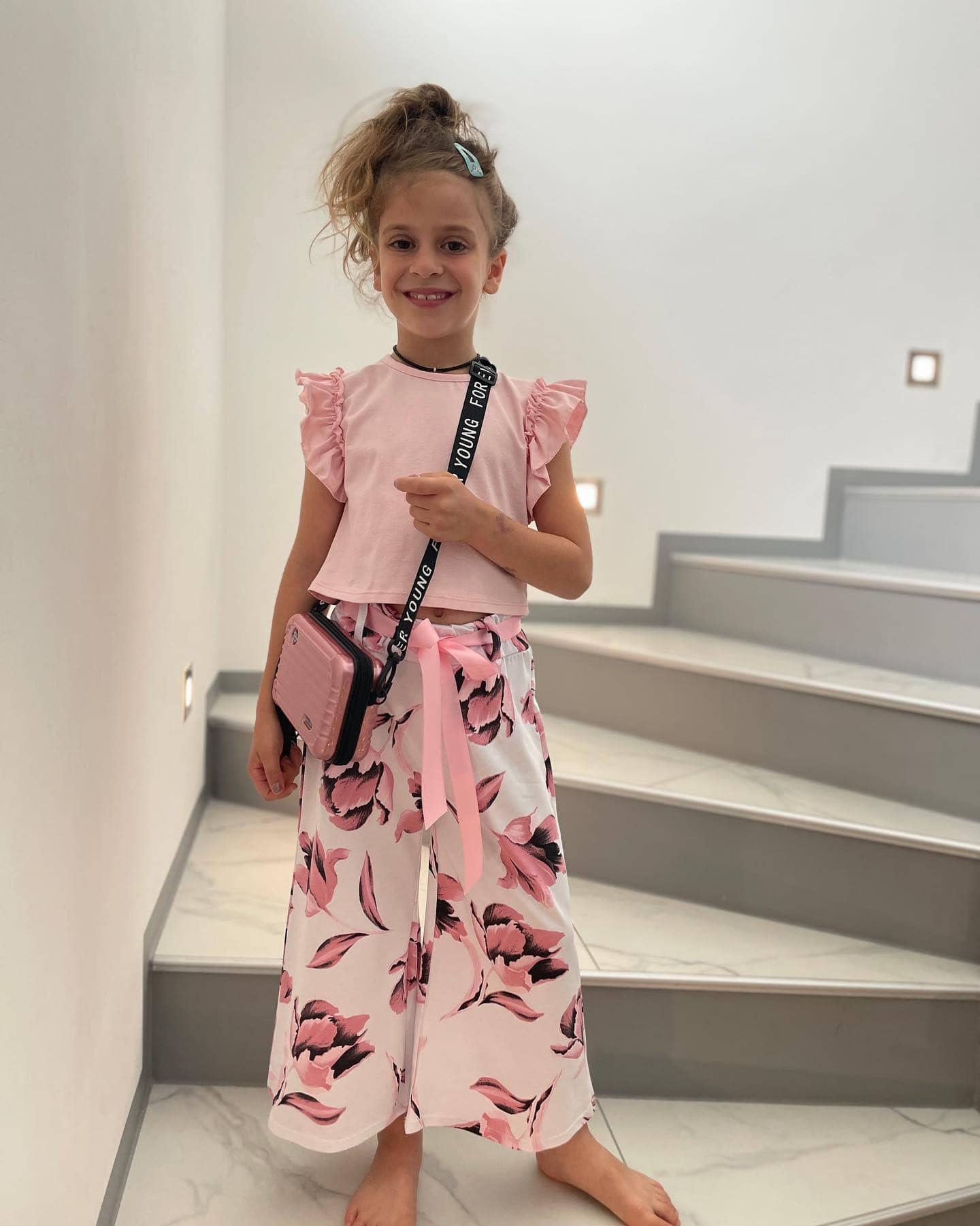Mädchenoutfit zum Schulbeginn in Rosa mit einfarbigem Shirt mit Flügelärmeln und einer weit ausgestellten Hose mit Blüten, dazu eine rosa Umhängetasche