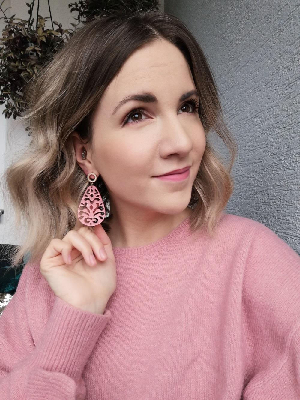 die Designerin von Heartwork aus Klagenfurt Verena Meleschnig präsentiert einen handgemachten Ohrring in der Farbe Rosa mit Ornamentmuster und einem goldenen Verschluss mit Strasssteinen