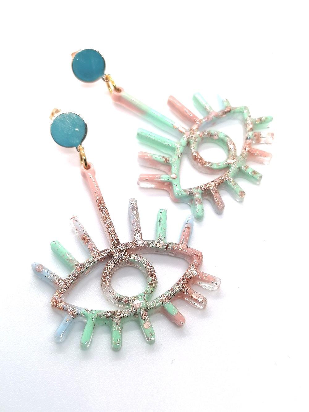 ein Paar handgemachte Ohrringe der Firma Heartwork aus Klagenfurt in Form von Irisaugen mit den Farben hellblau, mint, rose und rosegoldenem Glitzer