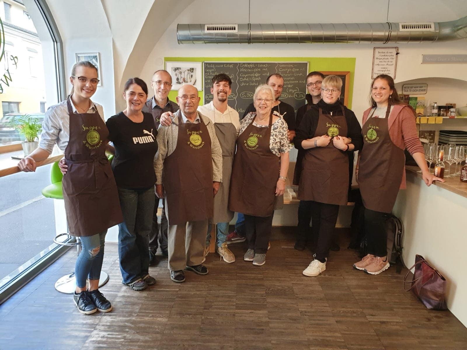 ein erfolgreicher Kochkurs bei Suppenglück in Klagenfurt, alle Teilnehmer strahlen in die Kamera und tragen Suppenglück-Kochschürzen