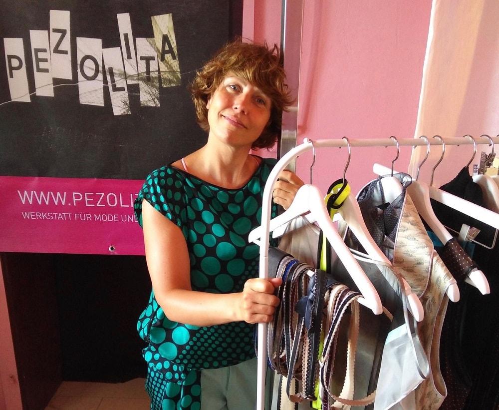 die Chefin persönlich steht an einer Kleiderstange mit ihren kreationen, Gürtel, Kleider, Oberteile und Röcke, handgeschneidert, Design aus Klagenfurt von Pezolita