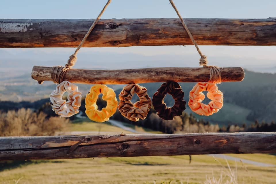 Haarbänder, Scrunchies der Firma Tinka aus Klagenfurt, handgemacht in verschiedenen Farben beige, gelb, braun, orange, caramel hängen auf einem Ast aufgewickelt, im Hintergrund eine Berglandschaft