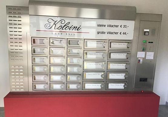 Tortenautomat mit verschiedenen Fächern aus Metall mit Beschriftung, welche Torte sich darin befindet, die Aufschrift verrät, dass die kleine Villachertorte 22€ und die große 44€ kostet, auf der rechten Seite der Box ist ein Münzeinwurf und ein Kartenterminal zu sehen