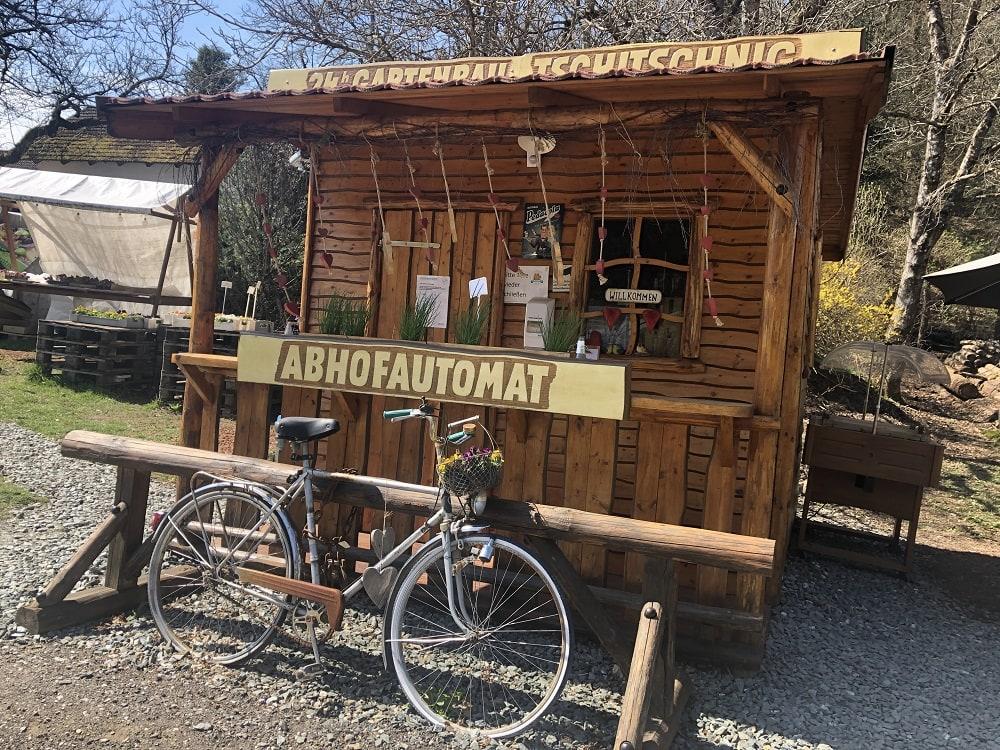 Außenansicht des 24h Abhofautomaten der Familie Tschitschnig aus Holz, davor steht ein mit Blumen geschmücktes Fahrrad